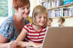 与使用便携式计算机的老师的学校学生在教室 免版税库存照片