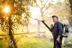 与使用喷雾器机器的农夫的农业细节为杀虫剂控制在果树园在日落时间 图库摄影