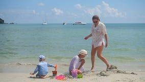 与使用在与玩具的沙滩的孩子和狗的愉快的家庭 热带海岛,在一热的天 股票录像