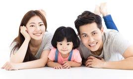 与使用在地板上的小女孩的家庭 免版税图库摄影
