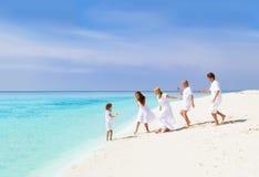 与使用在海滩的祖父母的愉快的家庭 免版税库存照片