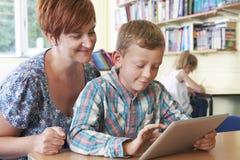 与使用数字式片剂的老师的学校学生在教室 免版税库存照片