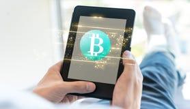 与使用片剂的人的Bitcoin 免版税库存图片