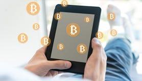 与使用片剂的人的Bitcoin 库存图片