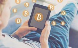 与使用片剂的人的Bitcoin 图库摄影