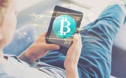 与使用片剂的人的Bitcoin 免版税库存照片