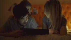 与使用片剂计算机的小儿子的愉快的家庭和谈在家说谎在床在睡觉前 影视素材