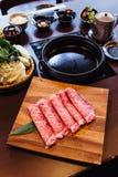与使高有大理石花纹的纹理的优质罕见的切片Wagyu A5牛肉在方形的木板材为Sukiyaki和沙埠服务 图库摄影