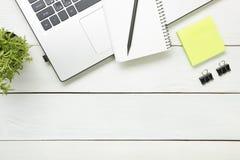 与供应的办公桌桌 顶视图 复制文本的空间 膝上型计算机、笔记薄、笔和花 库存图片