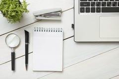 与供应的办公桌桌 顶视图 复制文本的空间 膝上型计算机,空白的笔记薄,笔,放大镜,计算器 免版税库存图片