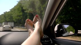 与便利-在汽车盘区的女性腿的旅行概念 窗口和女性腿有修脚特写镜头的反对 影视素材