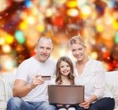 与便携式计算机和信用卡的愉快的家庭 库存照片