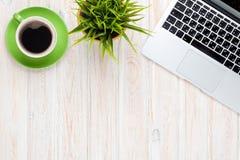 与便携式计算机咖啡杯和花的办公桌桌 库存照片