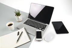 与便携式计算机的办公室桌,笔记本、数字式片剂和智能手机在现代两定调子白色和灰色背景 免版税库存图片