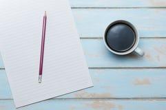 与便条的在颜色木地板上的咖啡和铅笔 免版税库存照片