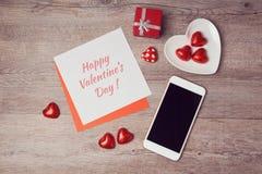 与便条纸和智能手机的情人节平的位置 在视图之上 免版税库存照片