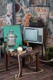 与俄国式茶炊的老电视,无线电和木桌 免版税库存图片