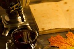 与俄国式茶炊,槭树叶子的茶静物画,在木背景 倒空开放一本老葡萄酒书 库存图片