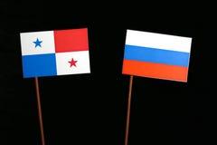 与俄国旗子的巴拿马旗子在黑色 图库摄影