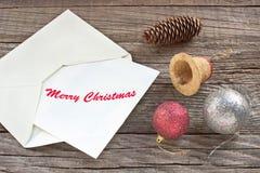 与信件、球和响铃的圣诞快乐在木背景 库存图片