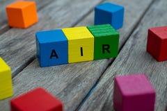 与信件的色的木立方体 词空气被显示,抽象例证 库存照片