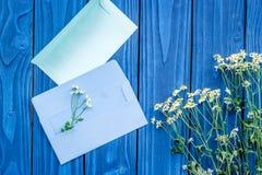与信封的花卉现代设计在蓝色木桌面看法嘲笑 免版税库存图片