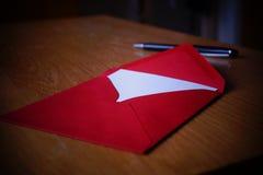 与信封的黑笔文字公告信件在木书桌上 免版税库存照片