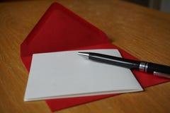 与信封的黑笔文字公告信件在木书桌上 免版税库存图片