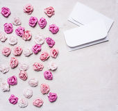 与信封,情人节边界的五颜六色的纸玫瑰,与正文白色木土气背景顶视图关闭 免版税图库摄影