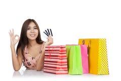 与信用卡和购物袋o的愉快的亚洲妇女展示OK 库存图片