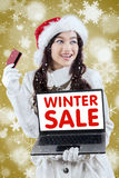 与信用卡的女孩网上购物在冬天销售 免版税库存图片