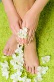 与修脚的美好的在绿色背景的脚和花 免版税图库摄影