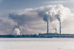 与倾倒在一条冻河之上的烟的管子的发电站 自由copyspace 免版税库存图片