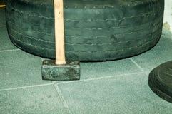与倾斜对中坚分子的力量训练的大卡车轮胎的木把柄的重的发嗡嗡声的东西在健身房 库存图片