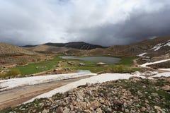 与倾斜的山风景包括通过熔化雪小vi 库存照片