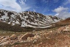 与倾斜的山风景包括通过熔化雪 免版税库存照片