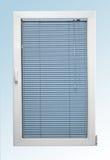 与倾斜的白色塑料窗口和两块玻璃和蓝色色盲 免版税图库摄影