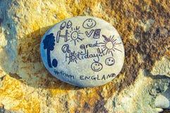 与假日文本的被绘的熔岩石头在白天的一个岩石 免版税库存图片