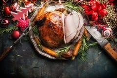 与假日欢乐装饰的传统切的烤给上釉的圣诞节火腿在黑暗的土气背景,顶视图 免版税图库摄影