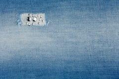 与假钻石的被撕毁的浅兰的牛仔裤 免版税图库摄影