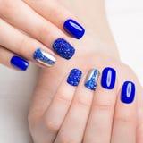 与假钻石的Beautifil蓝色修指甲 钉子设计 特写镜头 免版税库存图片