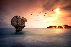 与偏僻的岩石雕塑的艺术在有飞鸟和一个灼烧的海岛剪影的海  免版税库存照片