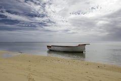 与偏僻的小船的海滩 免版税库存图片