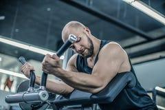 与做二头肌锻炼的完善的身体的英俊的肌肉男性模型 库存照片