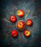 与做在土气木背景的巧克力涂层和切好的杏仁的红色苹果 库存照片