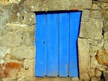 与做墙壁的石头的蓝色木门 库存图片
