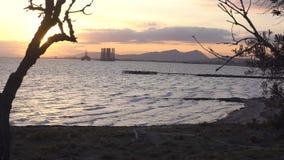 与做框架边界的树剪影的令人惊讶的海视图 与山和井架的海滨 4K录影 影视素材