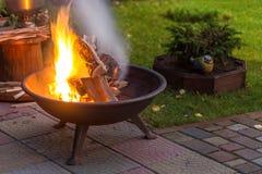 与做火花和烟的明亮的灼烧的木柴的一个便携式的壁炉在后院或庭院在房子附近 eveni的一个地方 库存图片
