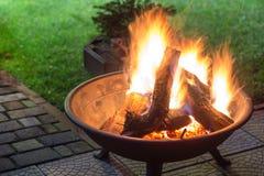 与做火花和烟的明亮的灼烧的木柴的一个便携式的壁炉在后院或庭院在房子附近 eveni的一个地方 免版税库存图片