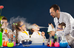 与做科学的科学家的愉快的孩子在实验室里试验 库存图片